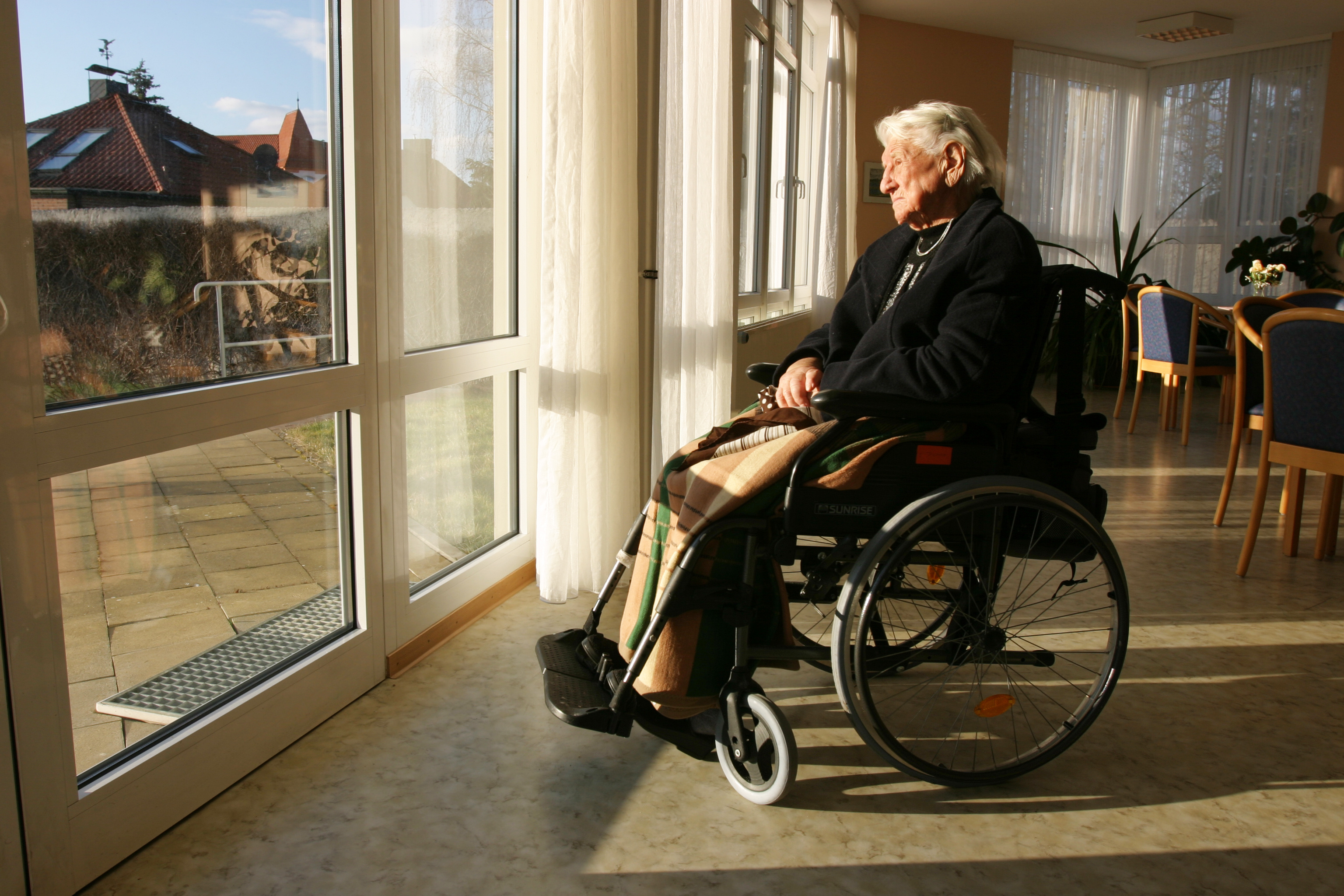 Elderly woman looking out window of lonely nursing home